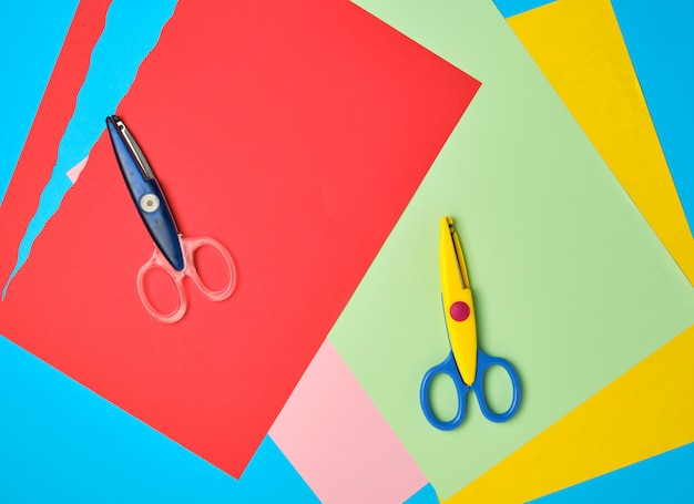 Par de tesouras de plástico e papel colorido para figuras de corte Foto Premium