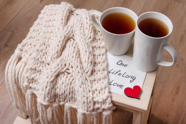 Par de xícaras, cachecol quente, em casa interior Foto Premium
