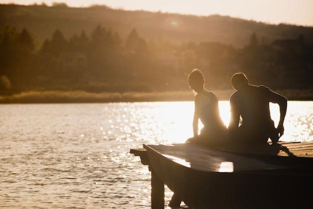 Par, desfrutando, pôr do sol, cais Foto gratuita