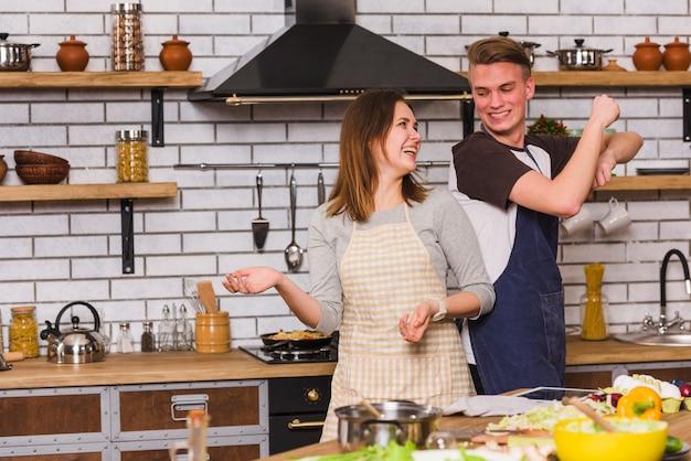 Par, em, aventais, tendo divertimento, e, dançar, em, cozinha Foto gratuita