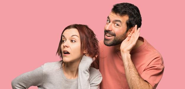Par, em, dia valentine, escutar, algo, sobre, isolado, fundo rosa Foto Premium