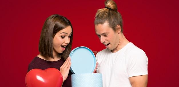 Par, em, dia valentine, segurando, caixa presente, em, cede, sobre, experiência vermelha Foto Premium