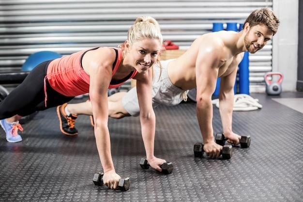 Par, fazendo, empurrar, cima, com, dumbbells, em, crossfit, ginásio Foto Premium