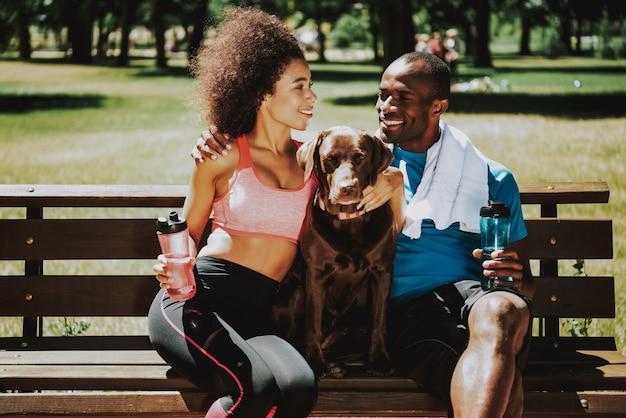Par feliz, em, sportswear, acariciando, adorável, cachorro marrom Foto Premium