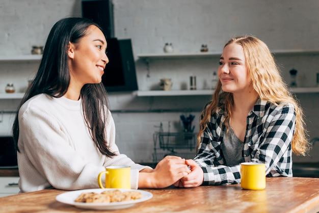 Par feminino, sentando tabela, em, cozinha Foto gratuita