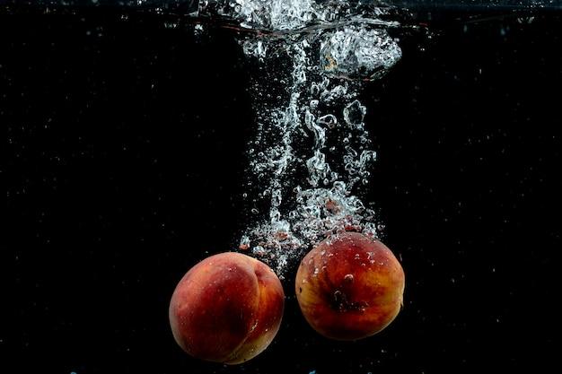 Par fresco de pêssegos na água Foto gratuita