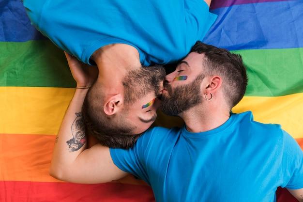 Par, homens, deitando, beijando, lgbt, bandeira Foto gratuita