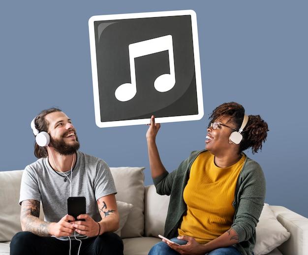 Par interracial, escutar música, e, segurando, um, nota musical Foto gratuita