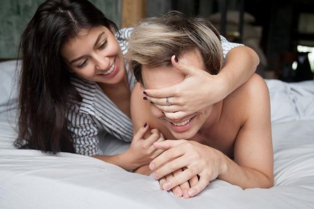 Par jogo, cama, mulher, encerramento, olhos homem, com, mãos Foto gratuita