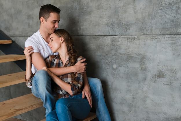 Par jovem, abraçando, ligado, passos, casa Foto gratuita