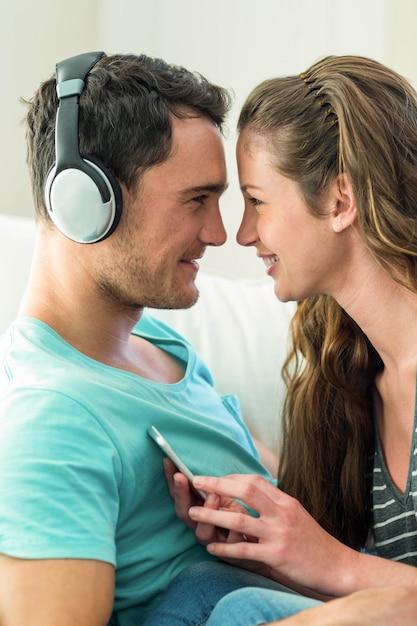 Par jovem, acaricie, enquanto, escutar música, ligado, telefone móvel, em, sala de estar Foto Premium