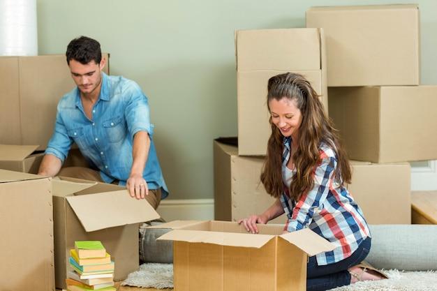 Par jovem, ajudando, um ao outro, enquanto, desembalando, caixas cartão, em, casa nova Foto Premium