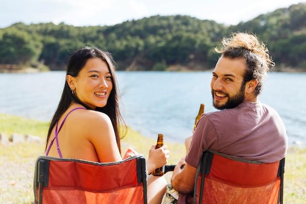 Par jovem, bebendo cerveja, ligado, banco Foto gratuita