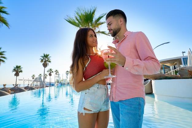 Par jovem, bebendo, coquetel, em, recurso piscina Foto Premium