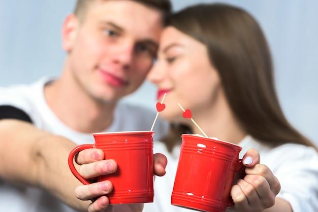 Par jovem, clanging, xícaras café Foto gratuita
