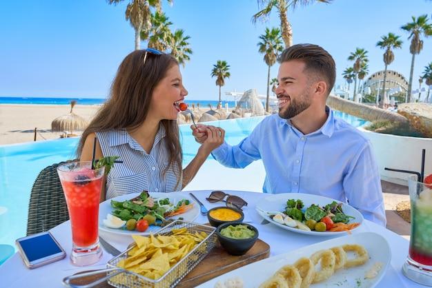 Par jovem, comer, em, um, restaurante piscina Foto Premium
