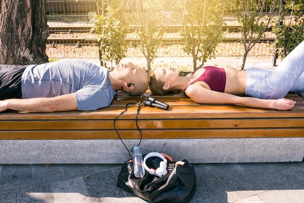 Par jovem, descansar, ligado, banco, com, equipamento esportes, parque Foto gratuita