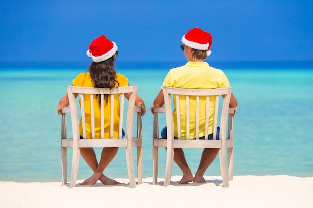 Par jovem, em, chapéus santa, relaxante, ligado, praia tropical, durante, natal, férias Foto Premium