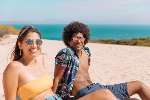Par jovem, em, óculos de sol, sentando praia, sorrindo, e, olhando câmera Foto gratuita