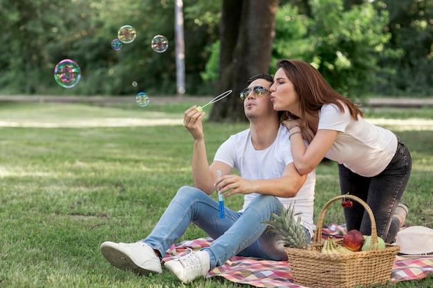 Par jovem, fazendo, bolhas, em, piquenique Foto gratuita