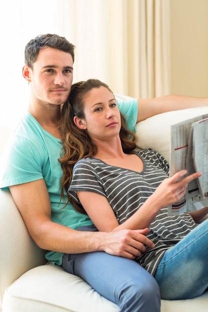 Par jovem, jornal leitura, ligado, sofá, em, sala de estar Foto Premium