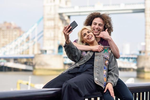 Par jovem, levando, selfie, fotografia, em, a, ponte torre Foto Premium