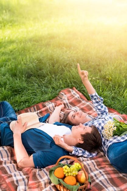 Par jovem, mentindo, ligado, cobertor, e, apontar, para, céu Foto gratuita