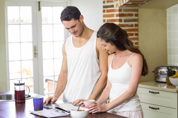 Par jovem, olhar, seu, organizador pessoal, enquanto, tendo, café manhã, em, cozinha Foto Premium