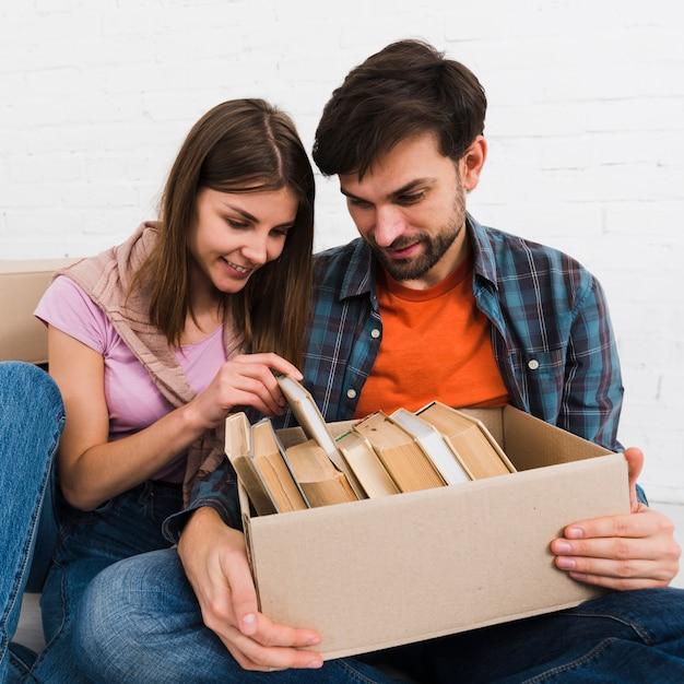 Par jovem, procurar, livros, em, a caixa papelão Foto gratuita