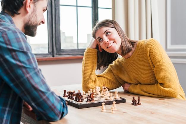 Par jovem, sentando, junto, jogando xadrez, casa Foto gratuita