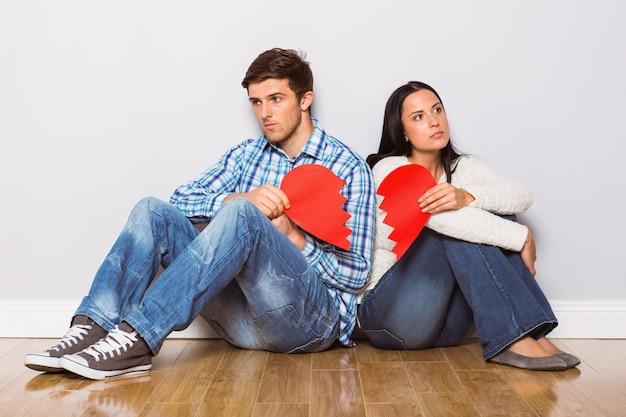 Par jovem, sentar chão, com, coração partido Foto Premium