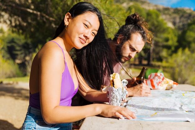 Par jovem, sentar-se tabela, com, mapa, e, lanche Foto gratuita