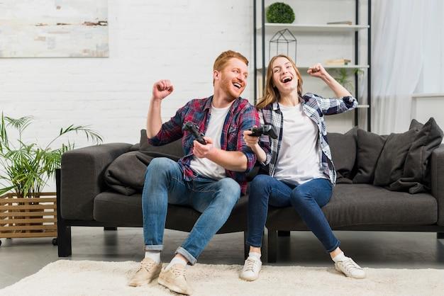 Par jovem, sentar sofá, jogando videogame, em, a, sala de estar Foto gratuita