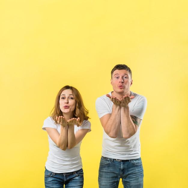 Par jovem, soprando, dela, beijos, contra, fundo amarelo Foto gratuita