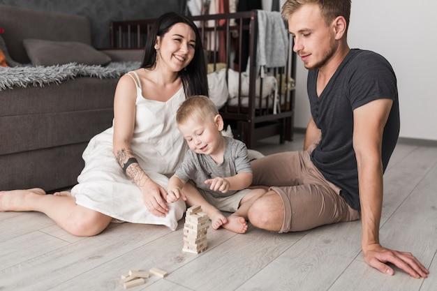 Par jovem, tendo divertimento, com, seu, filho pequeno, tocando, com, blocos madeira Foto gratuita
