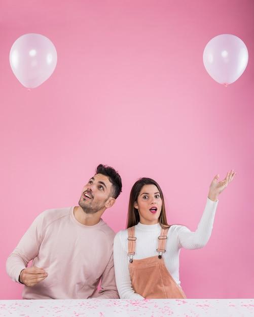 Par jovem, tocando, com, balões brancos Foto gratuita