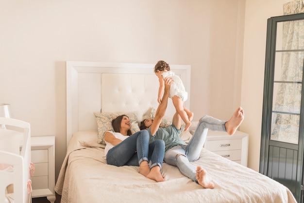 Par jovem, tocando, com, filha cama Foto Premium