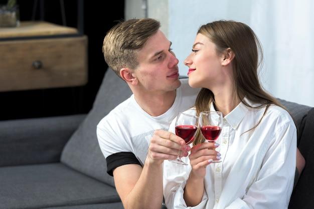 Par jovem, vinho bebendo, ligado, sofá Foto gratuita