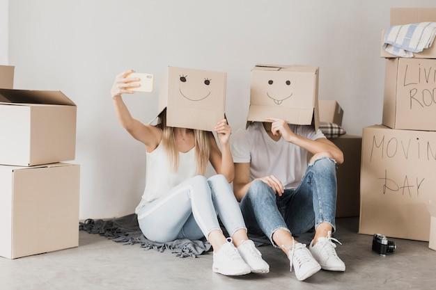 Par, levando, um, selfie, com, caixas papelão Foto gratuita