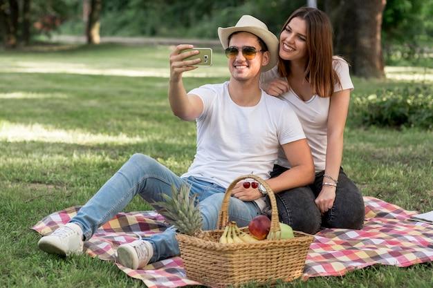 Par, levando, um, selfie, e, sorrindo, em, piquenique Foto gratuita