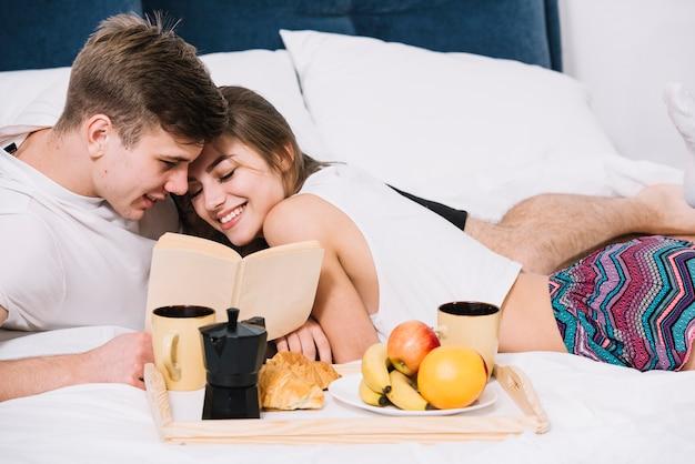Par, livro leitura, cama, com, bandeja, de, alimento Foto gratuita