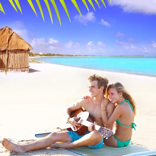 Par louro, sentando, em, um, praia, areia, violão jogo Foto Premium