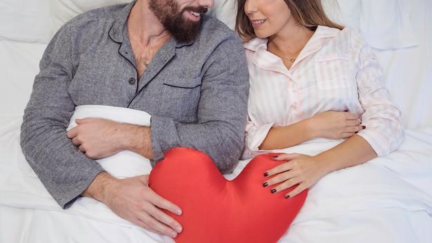 Par, mentindo cama, com, brinquedo, coração Foto gratuita