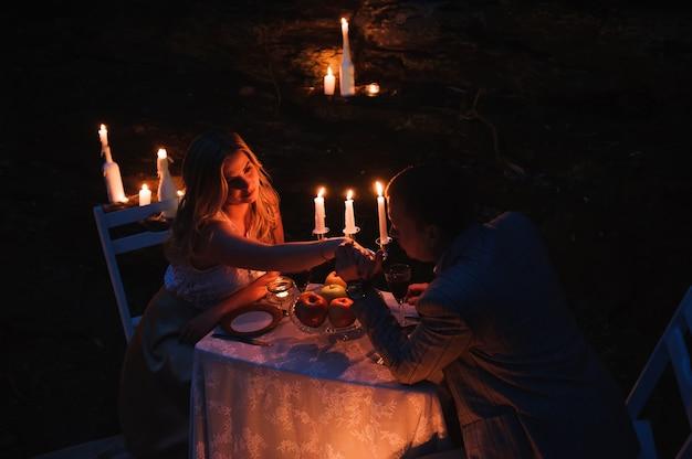 Par romântico de mãos dadas juntos sobre velas Foto Premium