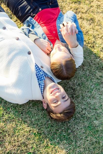 Par romântico deitado no gramado e jogar com as mãos Foto gratuita