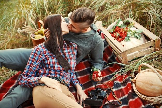 Par romântico sentado na grama e beijando Foto gratuita