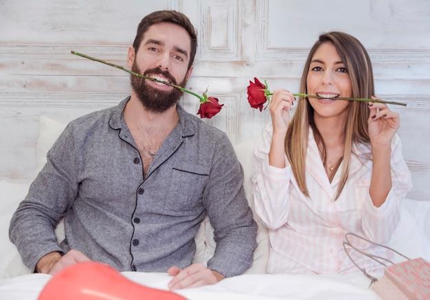 Par, segurando, rosas vermelhas, em, dentes Foto gratuita