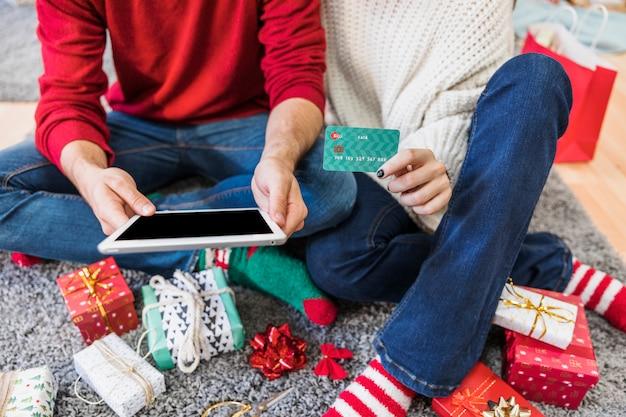 Par, sentando, com, tabuleta, e, cartão crédito, ligado, chão Foto gratuita