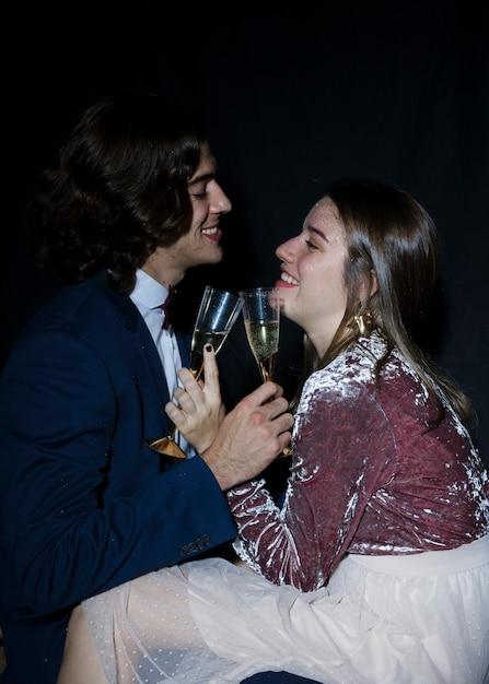Par, sentando, com, taças champanhe, em, mãos Foto gratuita