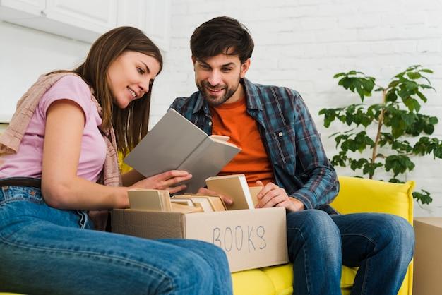 Par, sentando, ligado, sofá, livro leitura, com, caixa, em, a, sala de estar Foto gratuita